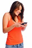 Attractive young brunette woman using her cell phone to send a text message
