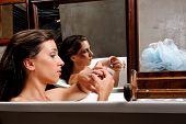 Woman relaxing in bathtub with mirror image of her with bruises on her face, a conceptual shoot of d