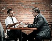 discussion in a coffee shop by two vintage businessmen