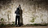 stock photo of graffiti  - Youngster with spray paint and an empty wall for graffiti - JPG
