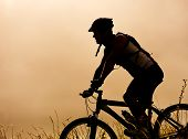 healthy fit man in silhouette rides his mountainbike outdoors at dusk, carefree bicycle fitness