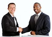 stock photo of million-dollar  - Happy businessmen shakes hands to seal the million dollar deal - JPG