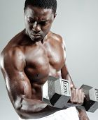 Well built muscular black man pumping iron