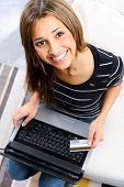 Woman is smiling and looking up to frame with laptop, after doing some online shopping