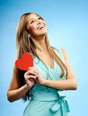 Beautiful young woman looks up and holds a red heart yearning for her love