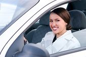 happy business woman in a car is looking at camera