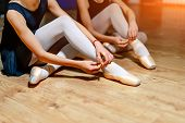 Young Ballet Dancers Tying Slippers Around Their Ankles On The Floor. Girls Sitting On The Floor And poster