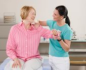 Physical therapist checking senior woman?s shoulder during medical checkup