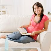 Casual young woman reading book on sofa at home
