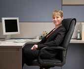 Happy, confident businesswoman sitting at desk in cubicle