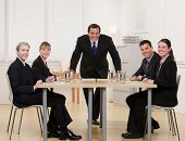 Co-workers sitting at conference table in conference room having meeting lead by supervisor