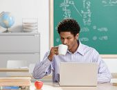 Teacher sipping coffee and working on laptop in school classroom
