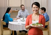 Woman holding appetizer and serving friends at elegant dinner party