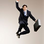 Excited businessman jumping in mid-air cheering and celebrating his success