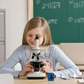 Young student in classroom peering into microscope during science class