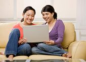 Barefoot friends enjoying using the laptop on sofa in livingroom