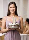 Generous woman holding lighted birthday cake about to surprise friends