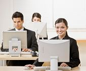 Businesswoman working on computer with co-workers in background