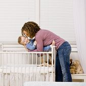 Devoted mother laying son down into crib for nap in bedroom