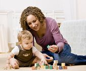 Devoted mother playing with alphabet blocks with her curious son