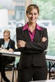 Confident businesswoman standing in front of co-workers in conference room