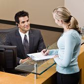 Friendly receptionist greeting woman at front desk