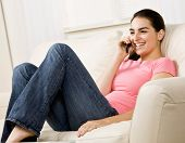 Relaxed, happy woman sitting in chair in livingroom talking on cell phone