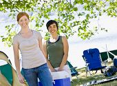 Women carrying cooler at campsite