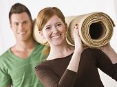 A young, attractive couple is carrying a roll of carpet.  They are smiling at the camera.  Horizontally framed shot.
