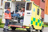 stock photo of ambulance car  - Paramedics putting patient man oxygen mask in ambulance car - JPG
