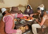Reenactment scene of the first Thanksgiving Dinner in Plymouth in 1621 with a Pilgrim family and a W