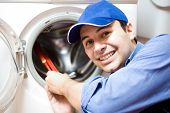 image of pipefitter  - Portrait of a technician repairing a washing machine - JPG