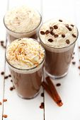 stock photo of whipping  - Ice coffee with whipped cream and coffee beans on a white table - JPG