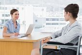 Businesswoman interviewing disabled candidate at desk in office