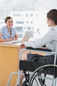 Businesswoman interviewing disabled job candidate in her office and smiling