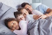 stock photo of pajamas  - Cute family sleeping together in bed - JPG