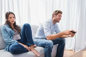 Man playing video games next to his annoyed partner sat on the couch