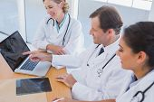 Smiling Doctor Kollegen Laptop-Bildschirm anzeigen, während sie zusammen arbeiten