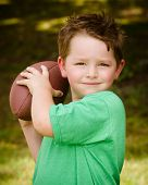 Child playing with football outdoors in yard