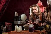 image of seer  - Male fortune teller with tarot cards waving hand over crystal ball - JPG