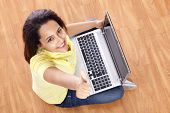 smiling young woman thumb up with laptop working at home