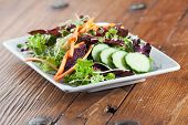 Colorful arugula salad in rustic environment