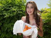 Pretty young woman holding fresh apricots