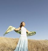 Woman standing with outstretched arms on field