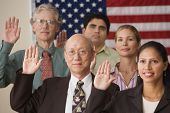 stock photo of solemn  - Adults raising their right hands before American flag - JPG
