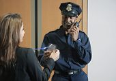 stock photo of credential  - Security guard checking businesswoman - JPG