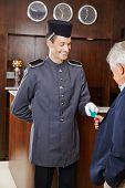 Helpful concierge giving senior man his hotel key card