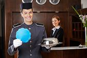 Friendly bellboy holding empty sign in hotel with receptionist behind counter