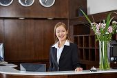 Happy female receptionist standing at hotel counter