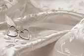 Wedding background of two silver hearts joined together with ribbon on elegant satin brocade fabric. Sepia toned macro with extremely shallow dof.